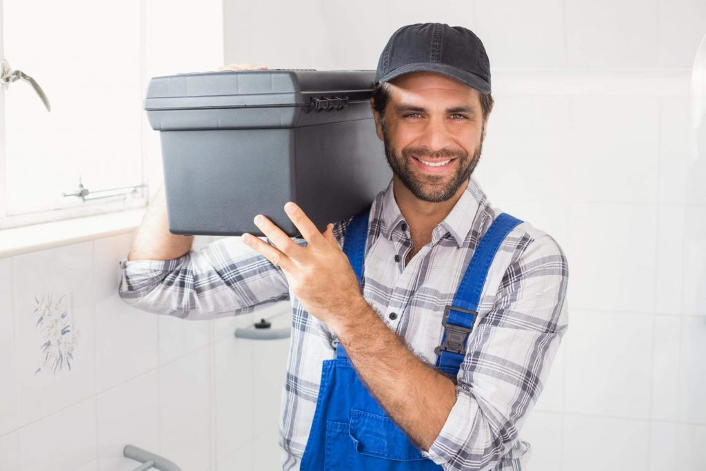 Male plumber with a black cap holding a toolbox on his shoulders whilst smiling at the camera