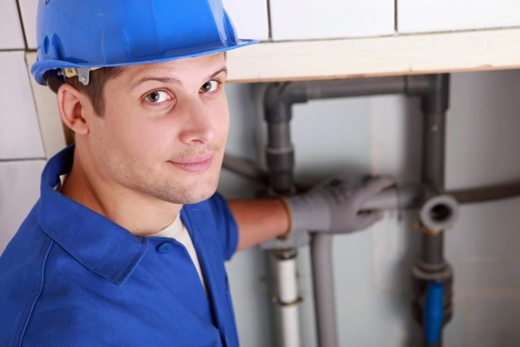 Young male commercial plumber looking at the camera whilst his finished plumbing work is shown in the background