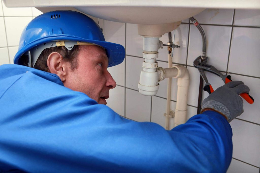 Older male plumber, with a blue helmet, coveralls and grey gloves, using a wrench to fix a sink's water supply