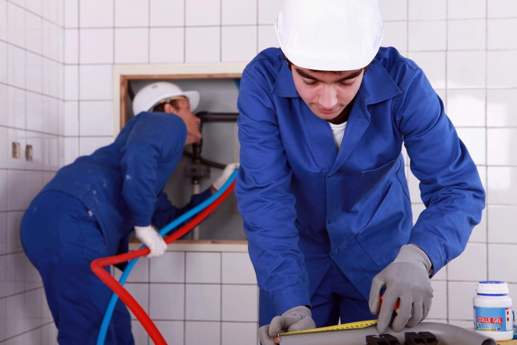 A junior and senior plumber with white helmets and blue coveralls, repairing emergency leaking pipes