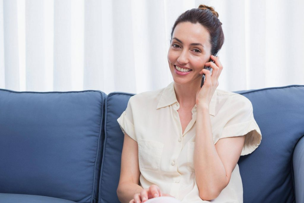 Female receptionist smiling whilst on a call, in order to book an appointment for a client