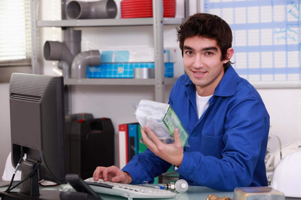 Young male plumber in front of a computer, holding a plumbing tool whilst having one hand on the keyboard