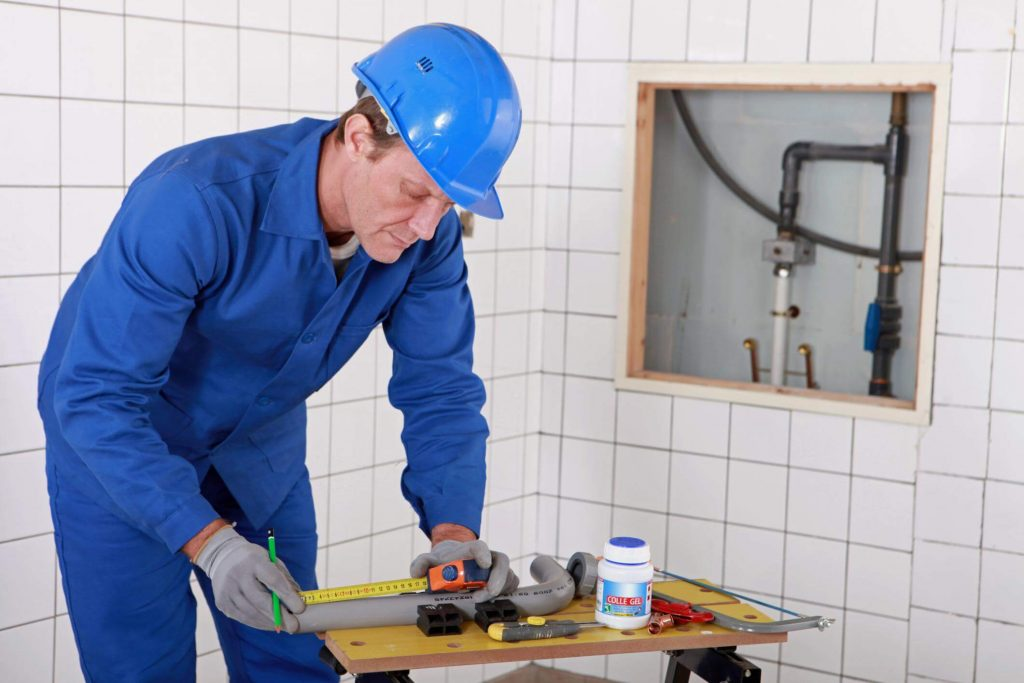 Older male plumber with a blue helmet and coveralls measuring pipes during a plumbing inspection
