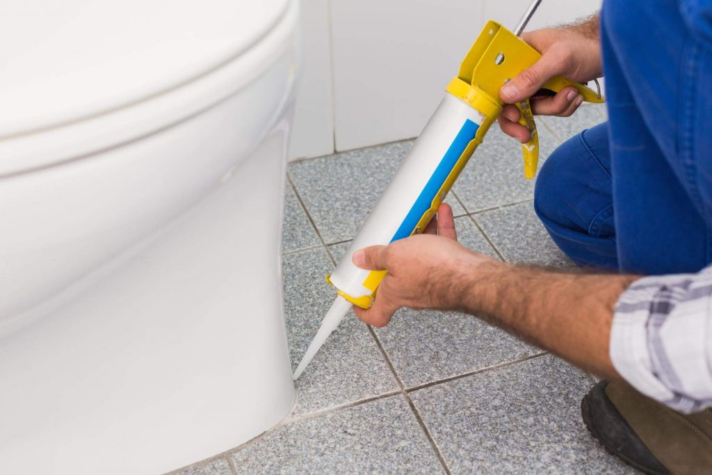 Male plumber on his knees gluing a toilet to the floor during a residential plumbing job