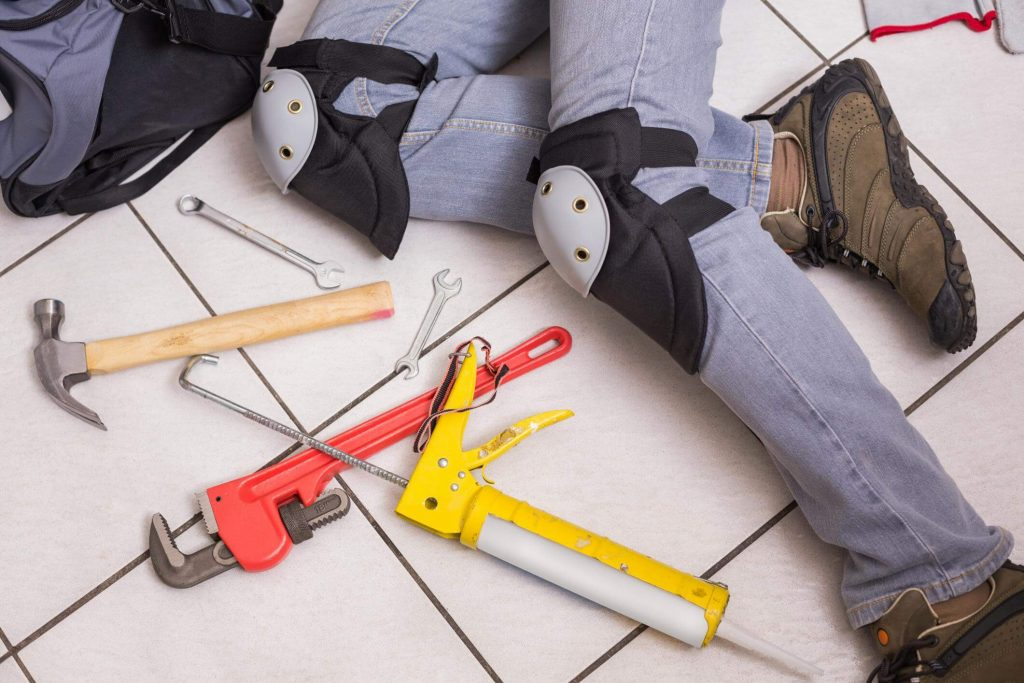 Plumber with knee protection, lying on the floor fixing a residential plumbing job, whilst having several plumbing tools on the floor