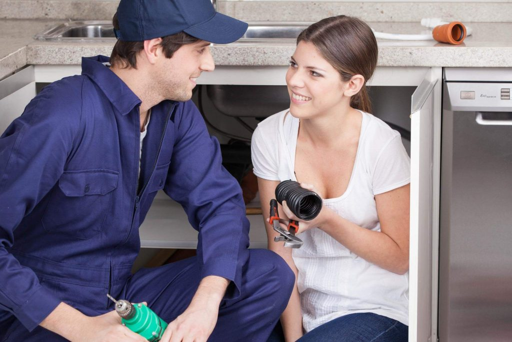 Smiling plumber in blue coverall and wearing a hat, explaining to a smiling female client what was wrong with the plumbing in the kitchen