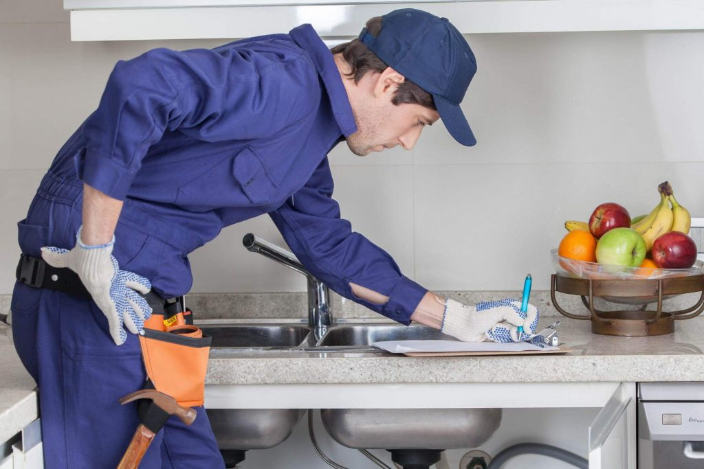 Male plumber in blue writing out a service form on the kitchen counter